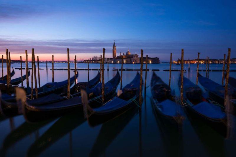 Gondolas moored at dock with santa maria della salute in background
