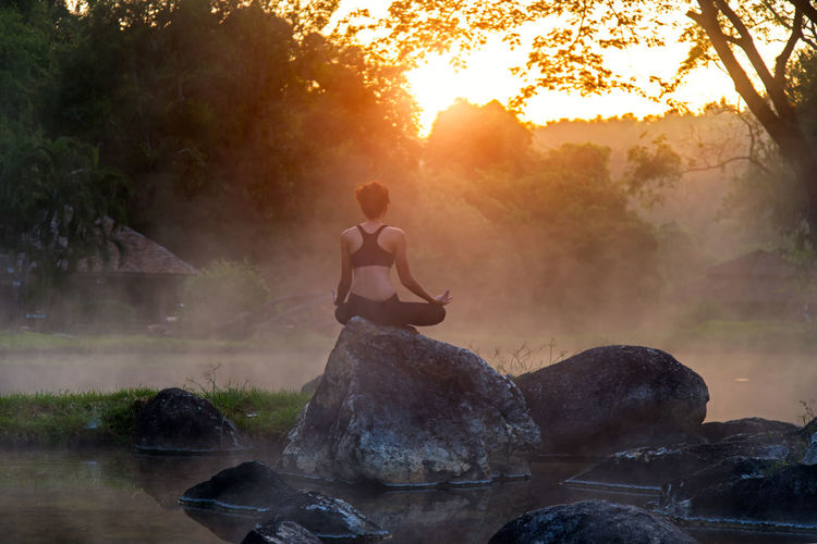 Man sitting on rock against trees at sunset