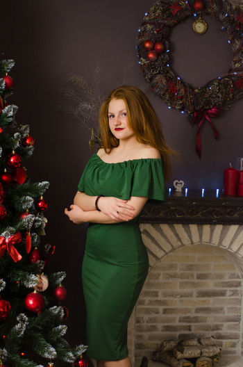 Portrait of young woman standing by christmas tree at home