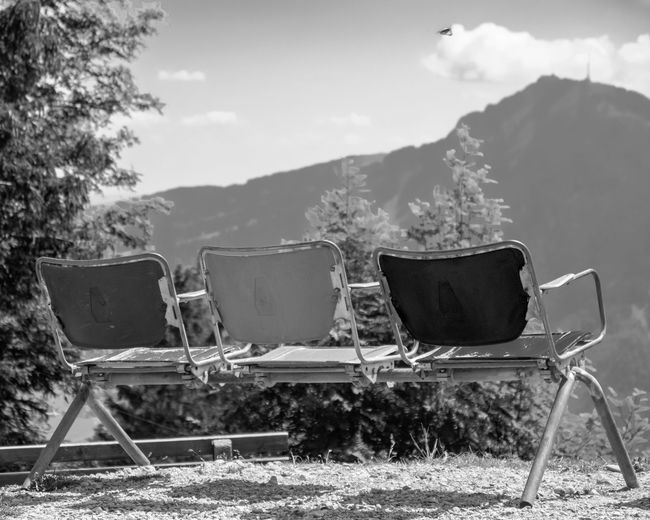 Empty chairs on land against sky