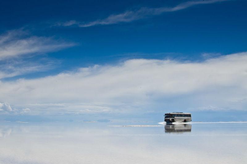 Lone boat in calm blue sea against clouds
