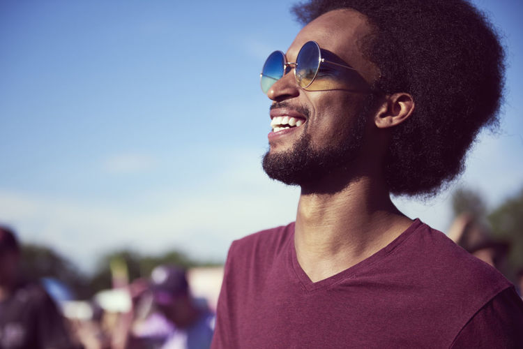 Close-up of smiling young man wearing sunglasses against sky