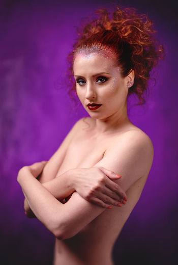 Portrait of sensuous woman covering breasts with hand against purple background