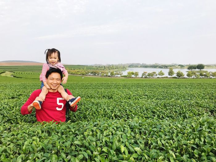 Daughter riding father neck Warm Copy Space Positive Emotion Red Green Smile Outdoors Sky Father Family Happy Field Childhood Child Real People Sky Plant Land Looking At Camera Green Color Nature Day Lifestyles Leisure Activity Girls Portrait Front View Beauty In Nature This Is Family