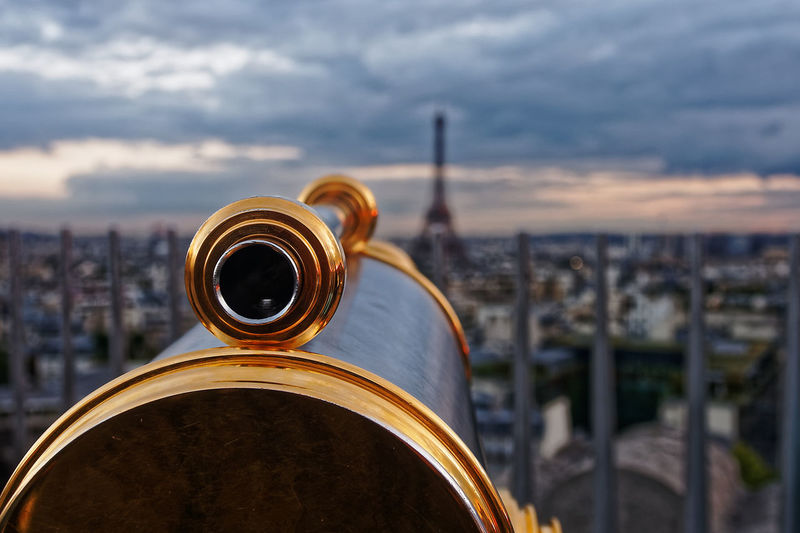 Close-Up Of Coin Operated Binoculars Over Cityscape Against Sky