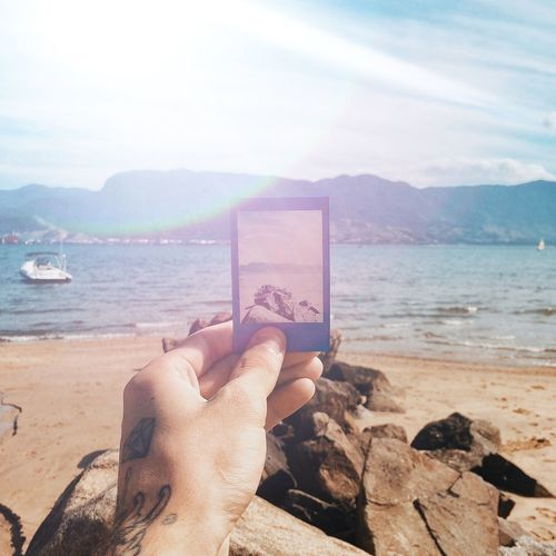 Cropped Image Of Hand Holding Picture Frame At Beach Against Sky