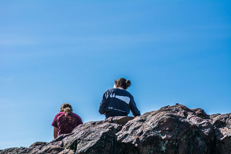 Adventure Backpack Blue Children Clear Sky Climbing Day Friendship Hiking Leisure Activity Lifestyles Low Angle View Nature Outdoors Real People Rear View Rock - Object Scenics Sitting Sky Standing Togetherness Two People Vacations