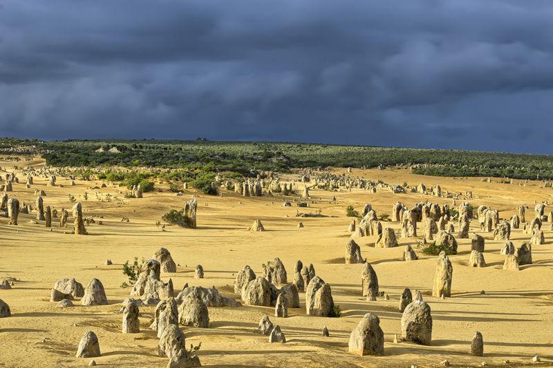 Rocks on sand at beach against sky