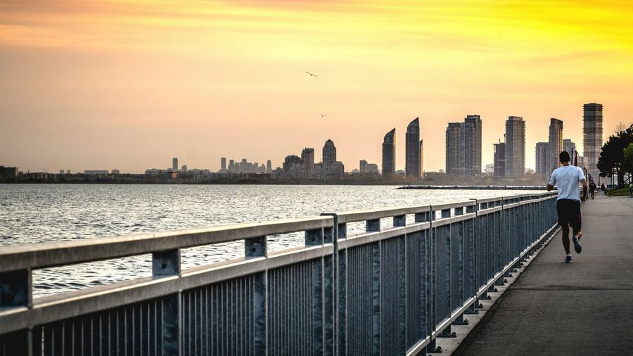 Rear view of woman walking on bridge in city during sunset