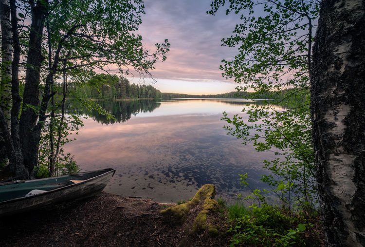 Scenic landscape with idyllic lake view and boat at summer evening in Finland Calm Finland Rowboat Tranquility Beauty In Nature Boat Cloud - Sky Idyllic Lake Lake View Landscape Nature No People Non-urban Scene Outdoors Plant Reflection Scenics - Nature Sky Standing Water Sunset Tranquil Scene Tranquility Tree Water