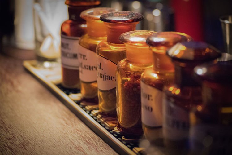 Bar: Dry ingredients for cocktails Bottle Close-up Focus On Midground Glasses Healthcare And Medicine Illöuminate In A Row Indoors  Ingredients For Cocktails Night No People Text Vignette Wood - Material