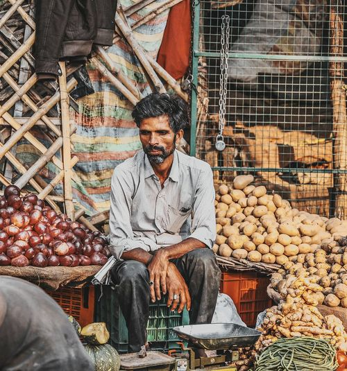 Mature Man Selling Vegetables While Sitting At Market