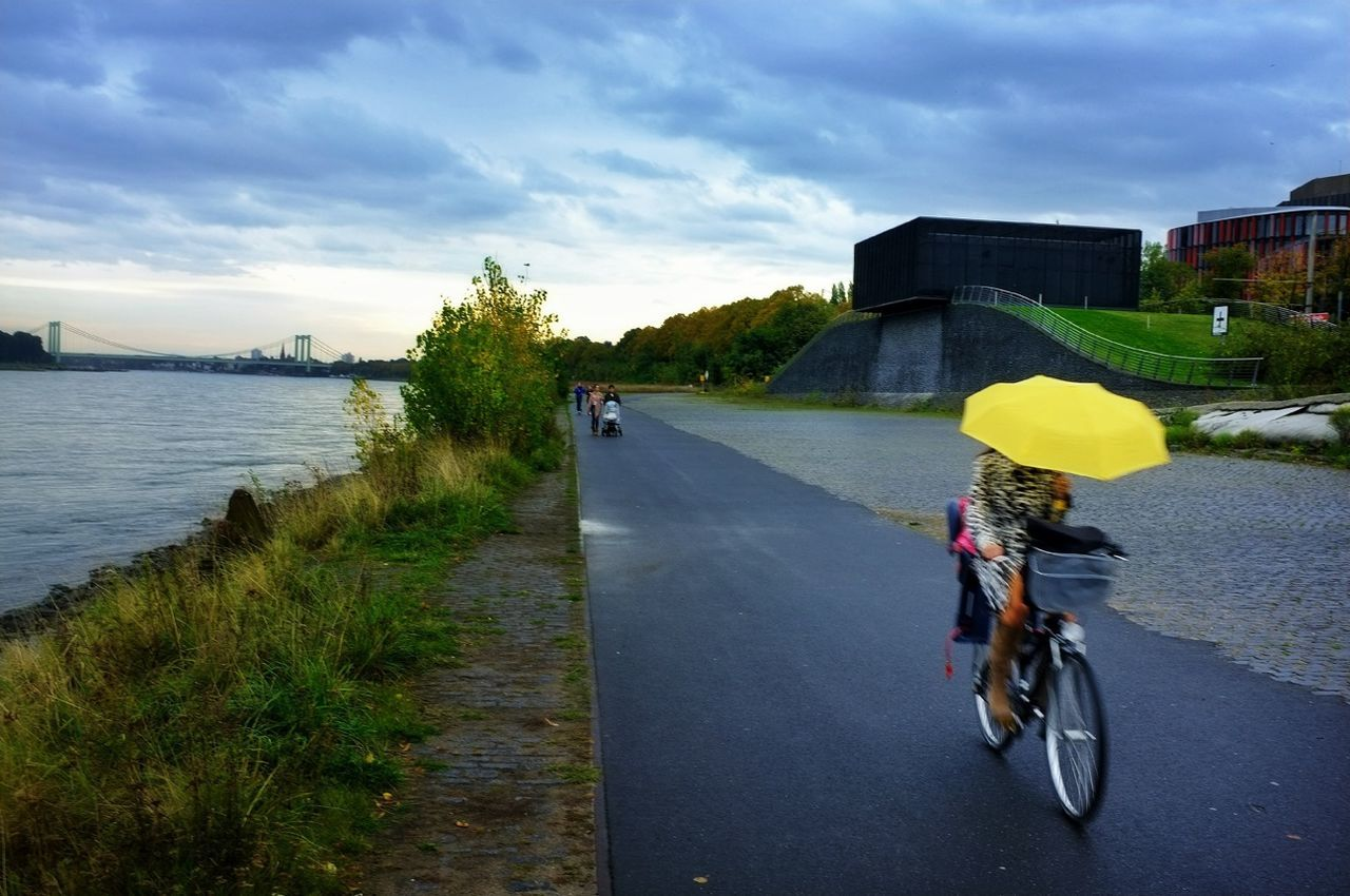 Woman with umbrella bicycling by calm river