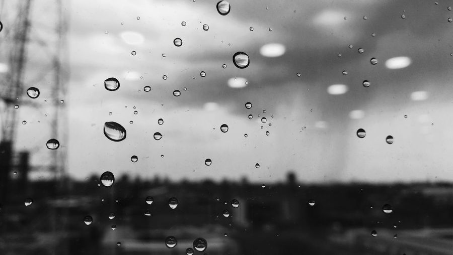Close-up of water drops on window against sky