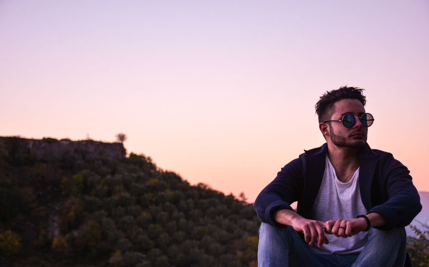 Portrait of man wearing sunglasses against sky during sunset