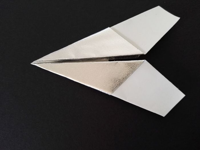 Close-up of paper airplane against black background