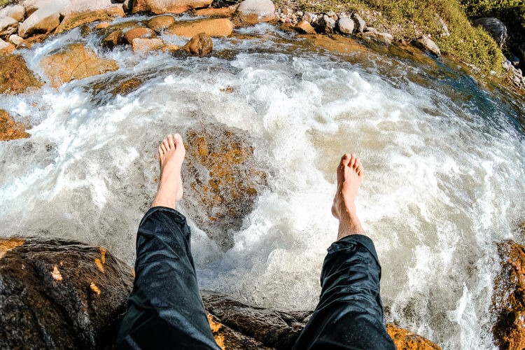 Water One Person Flowing Water Jeans High Angle View barefoot Nature Leisure Activity Personal Perspective Human Leg Outdoors Motion Running Water Waterfall Hiking Water Splash Analogue Sound