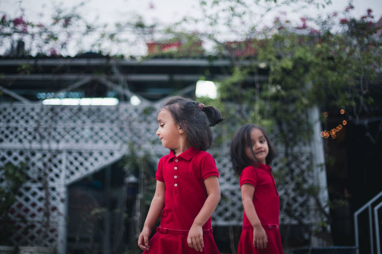 Twin Sisters Standing In Backyard