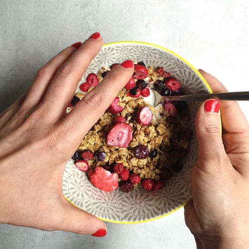Cropped Image Of Woman Holding Breakfast Bowl On Table