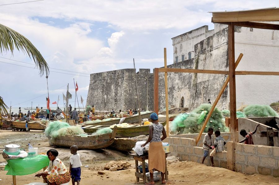 Africa Architecture Beach Building Exterior Built Structure Castle Cloud - Sky Coastline Colonial Colonial Architecture Colonialism Fishing Boat Fishing Village Ghana Large Group Of People Nature Outdoors Real People Sky Slave Trade Slavery Standing Traditional Culture Water Poverty