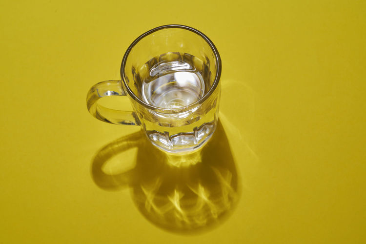 Close-up of wineglass on table against yellow background