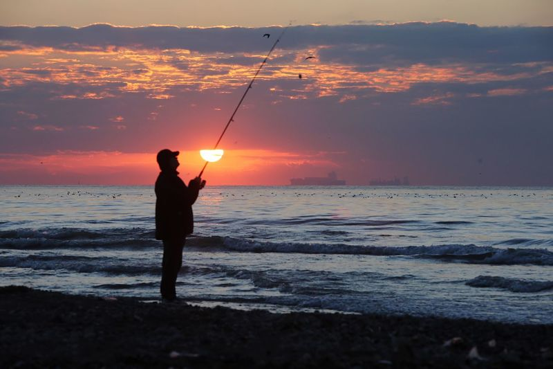 Sunset and fishing Sea Water Sunset Rod Sky Fishing Fishing Rod Activity Beach One Person Beauty In Nature Leisure Activity Standing Real People Scenics - Nature Land Holding Silhouette Horizon Horizon Over Water