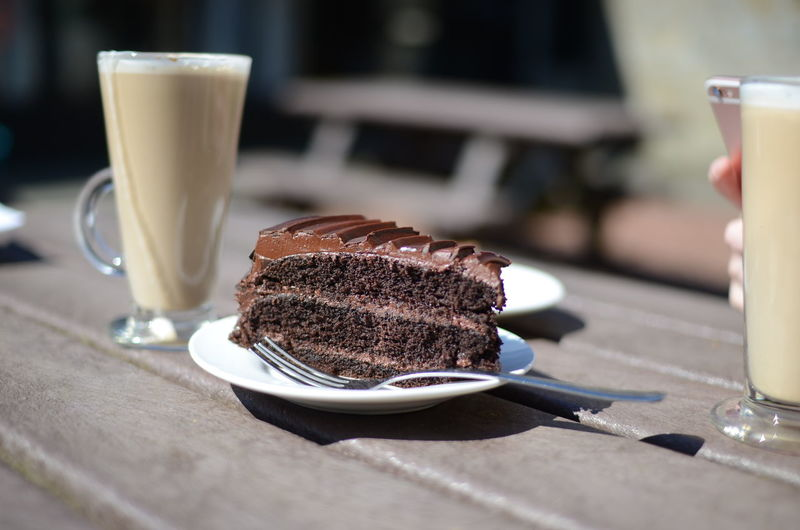 Close-up of chocolate cake with latte served on table at cafe