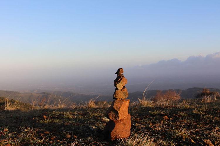 Stack Of Stones On Landscape Against Sky