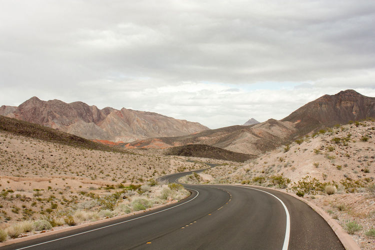 Desert Road Beauty In Nature Cloud - Sky Curve Empty Landscape Mountain Mountain Range Mountain Road Nature Nevada No People Outdoors Physical Geography Road Roadtrip Scenics Sky The Way Forward Tranquil Scene Tranquility Transportation Winding Road