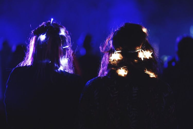 Rear view of women with illuminated decorations on hair