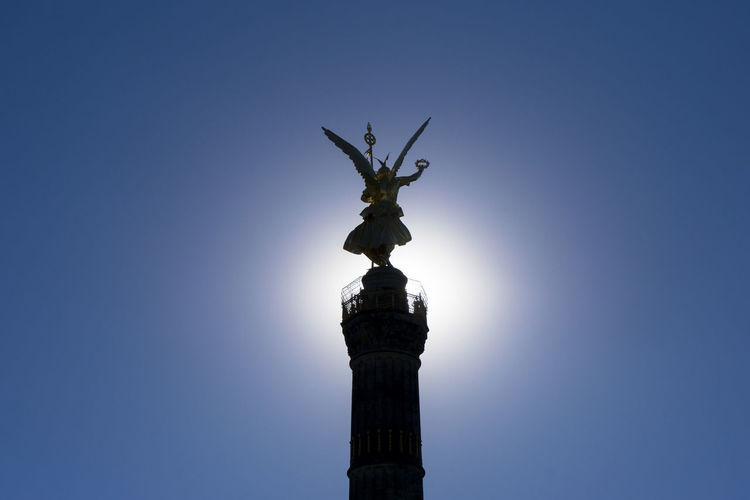 Low angle view of silhouette victory column against clear sky on sunny day