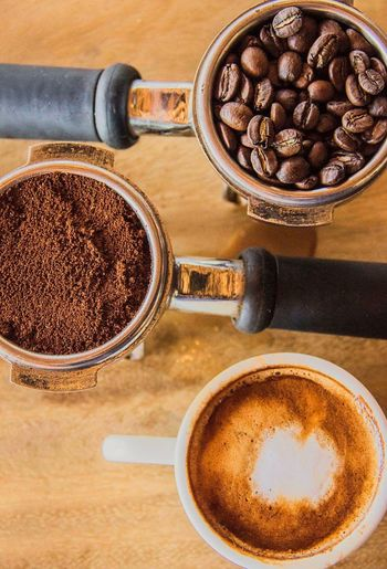 High angle view of coffee cup by beans and powder in portafilter on table