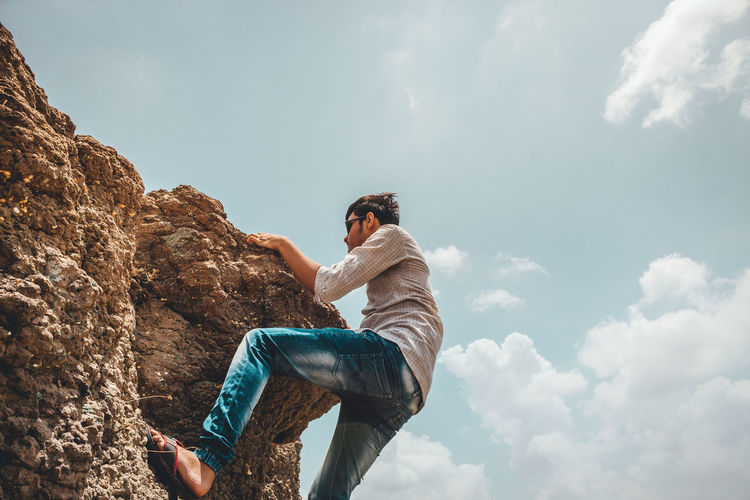 Low angle view of young man clambering on rock against sky during sunny day