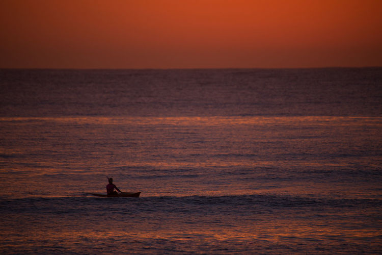 Silhouette man kayaking in sea against sky during sunset
