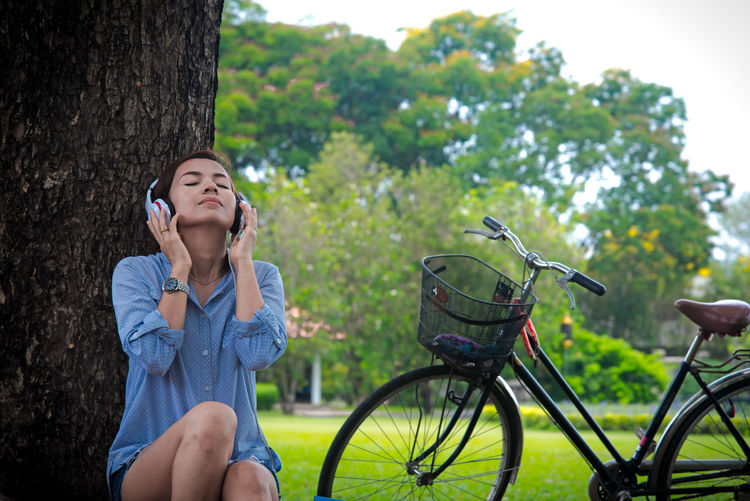 Young woman sitting on bicycle against trees