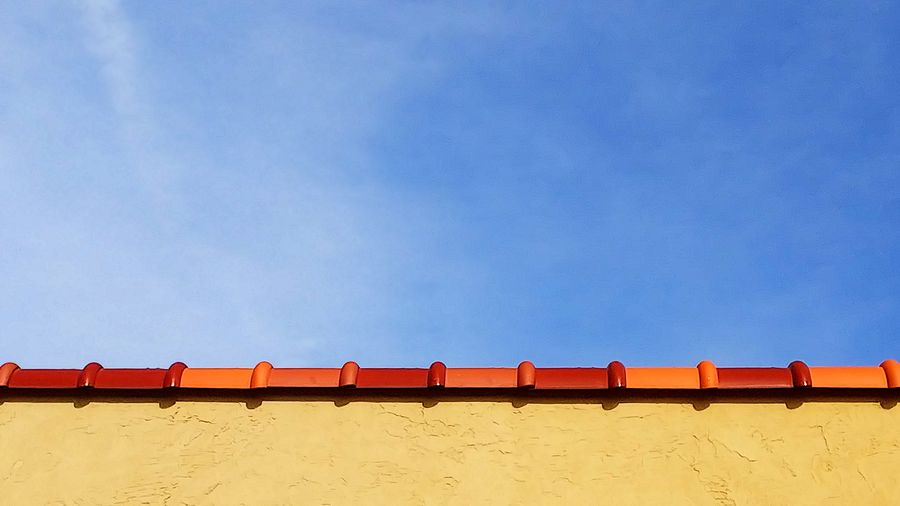Low angle view of rooftop against blue sky