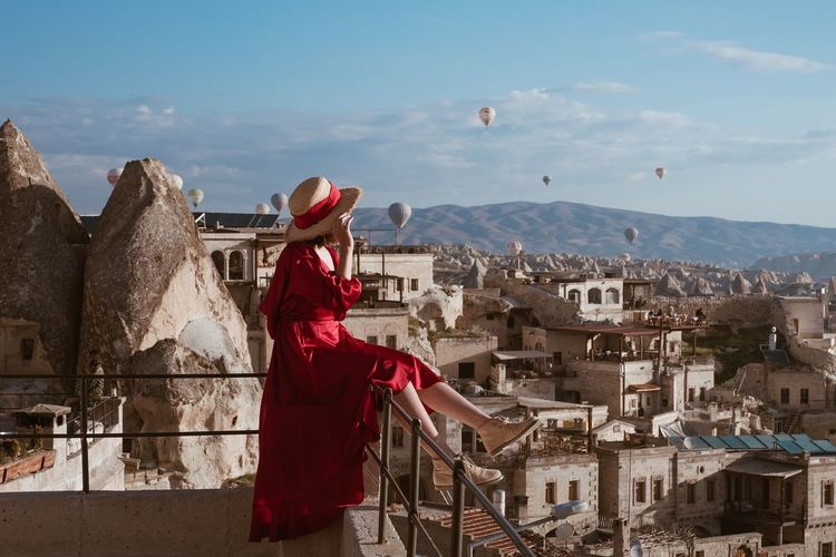 Woman standing by buildings in city against sky