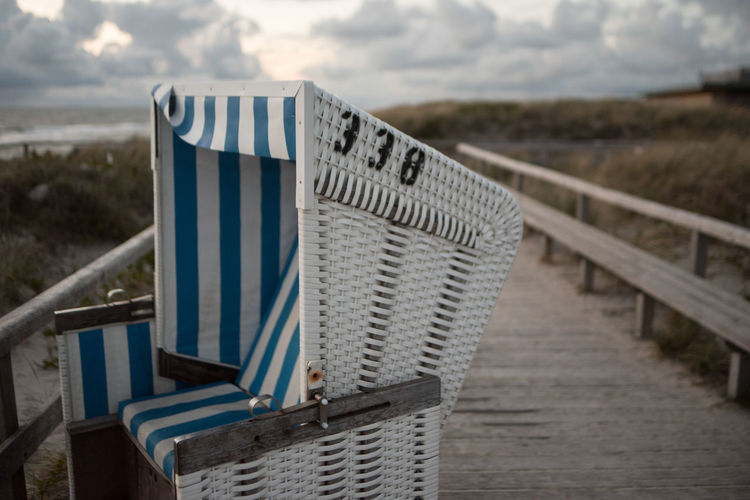 Close-up of beach chair on wooden post