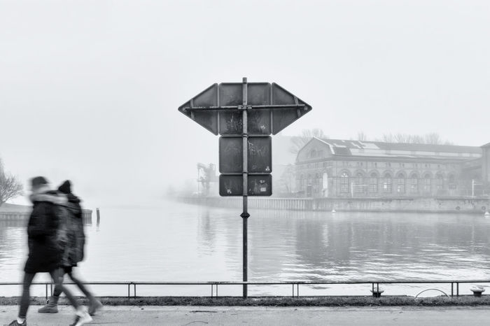 Two women passing by at junction of Havel and Spree River on a foggy day in Spandau in Berlin, Germany Berlin Color Image Confluence Foggy Days  Germany🇩🇪 Havel River Horizontal Junction Motion Capture No People Outdoors Photography Signs Spree River Two People Unrecognizable People Women