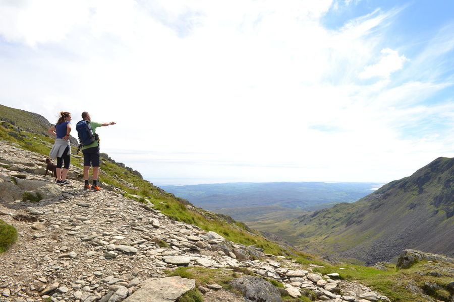 Couple of hikers on The Old Man of Coniston, The Lake District, Cumbria, United Kingdom Adventure Backpack Beauty In Nature Casual Clothing Day Hiking Lake District Lake District National Park Leisure Activity Lifestyles Mountain Nature Old Man Of Coniston Outdoors Real People Rear View Scenics Sky Standing Togetherness Tranquil Scene Tranquility Two People Vacations Walking