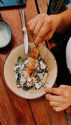 Woman eating healthy salmon cuscus salad