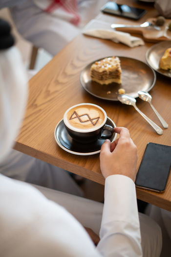 Coffee on Wooden Table in Cafe Food And Drink One Person Holding Table Indoors  Human Hand Real People Drink Adult Human Body Part Women Hand High Angle View Food Refreshment Lifestyles Mug Coffee Cup Freshness Preparation  Crockery Tray Ijas Muhammed Photography