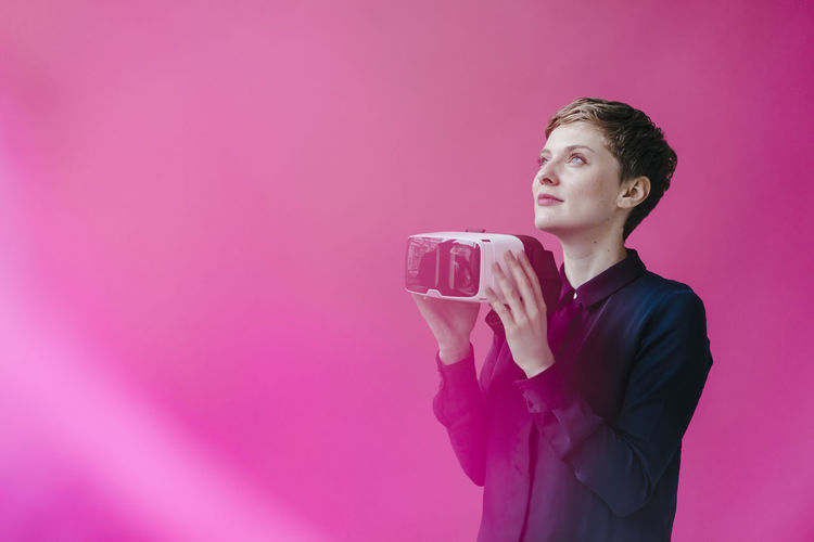 Full length of young man drinking glass against pink background