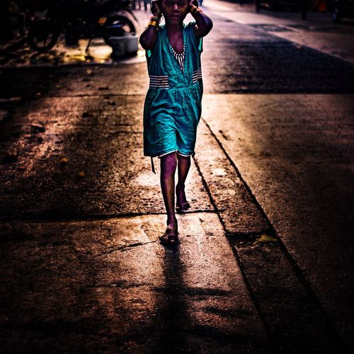 Rising rays on street of Mumbai One Person Lifestyles Women Real People Leisure Activity Outdoors Only Women One Woman Only People Night Low Section Adult