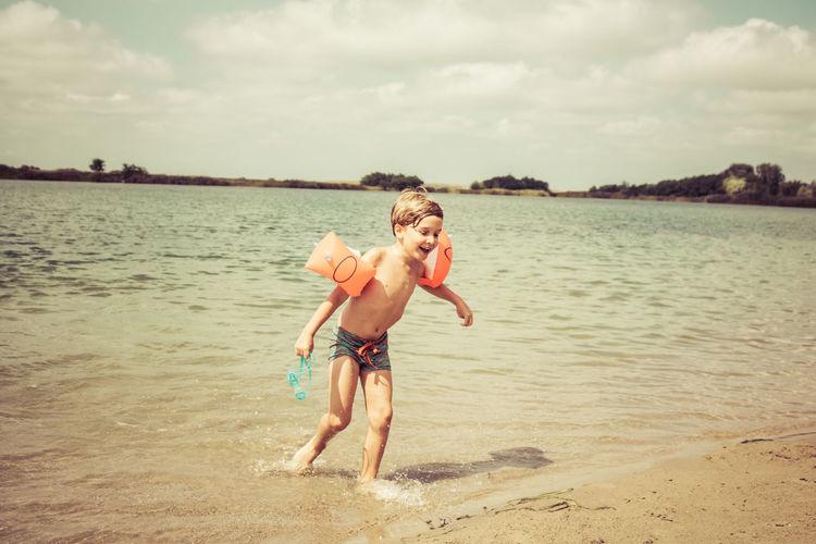 Full length of shirtless boy on lakeshore against sky