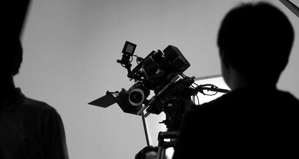 Rear view of operator using camera in studio