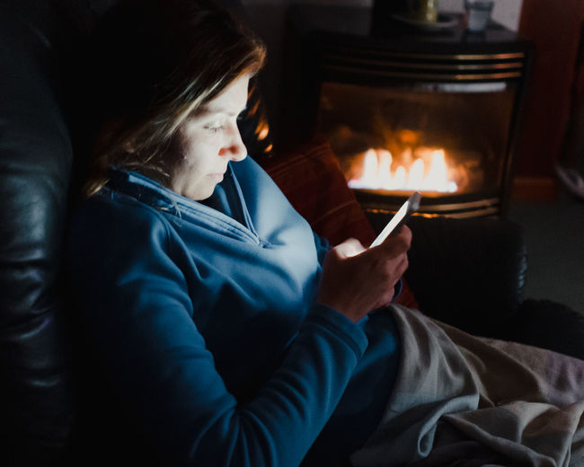 High angle view of woman using smart phone while sitting on sofa at home