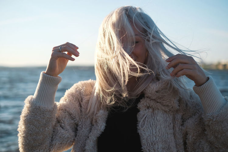 Lifestyle portrait of young blonde woman at sunset with sea background City Blond Hair Communication Connection Far Hair Hairstyle Holding Leisure Activity Lifestyles Long Hair Mobile Phone One Person Outdoors Portrait Real People Sea Using Phone Warm Clothing Windy Wireless Technology Women