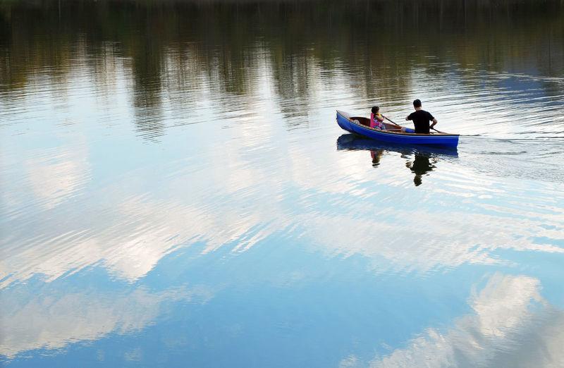High Angle View Of Man And Girl On Boat On Lake
