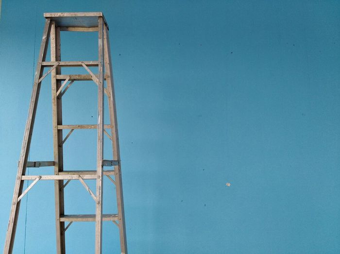 Close-up of ladder against blue wall